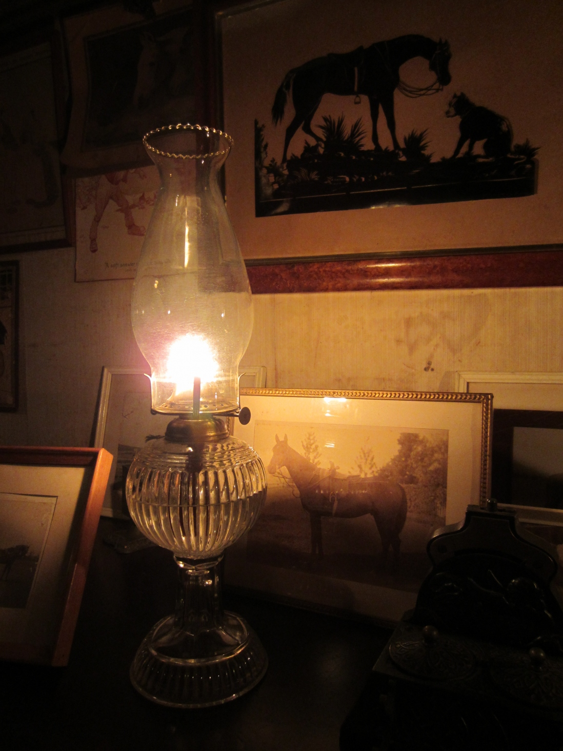 Kerosene lamp illuminating a framed picture and wallpaper behind.