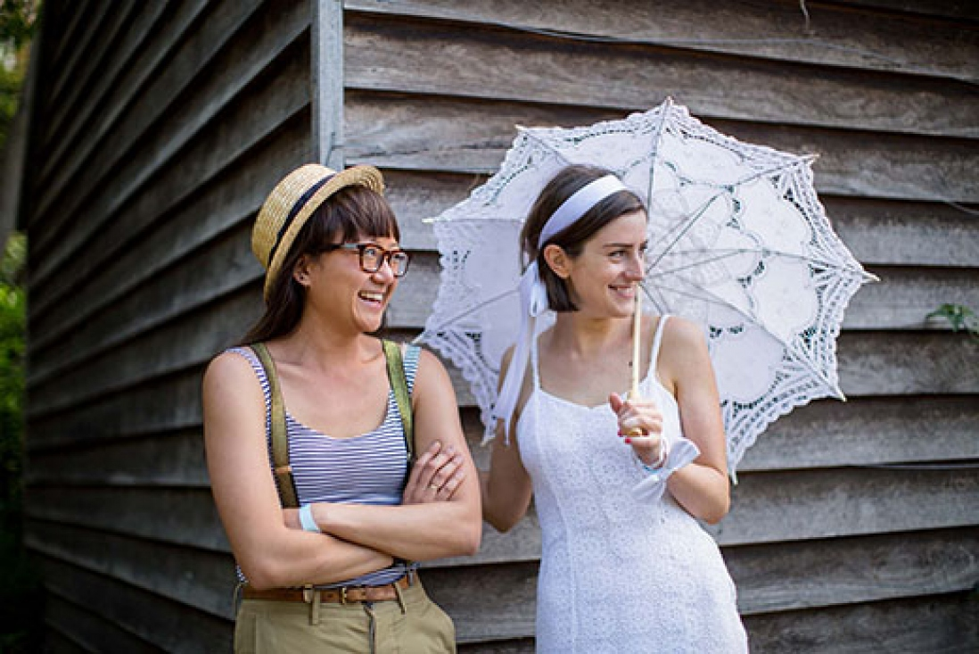 Two women standing in front of wooden planked wall.