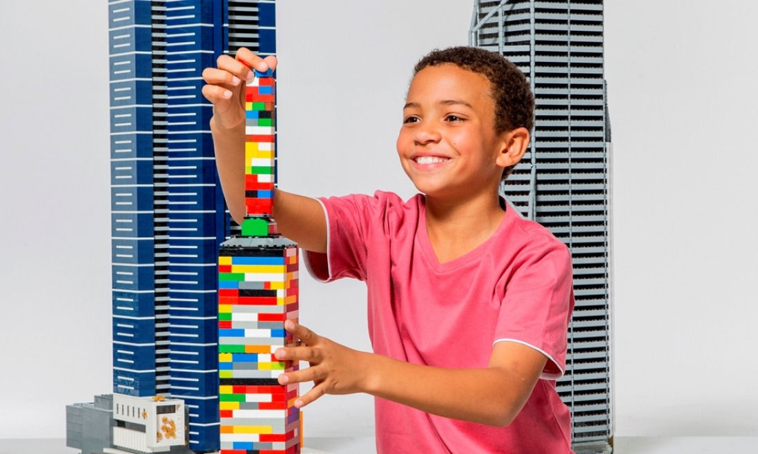 Boy creates building from LEGO in front of models of Eureka Tower and Central Park Tower.