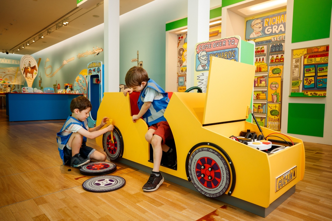 Exhibition view of two boys changing the wheels of a toy car