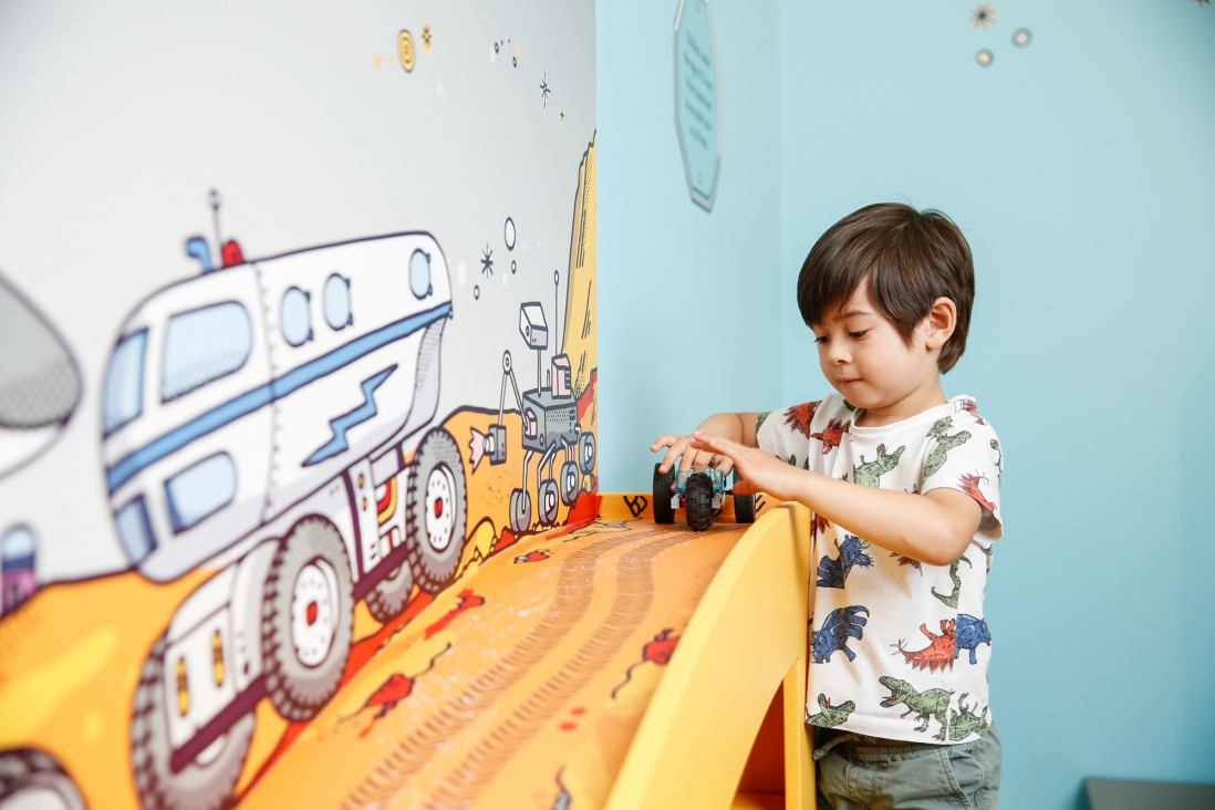 Exhibition view of a boy playing with car made of Lego bricks