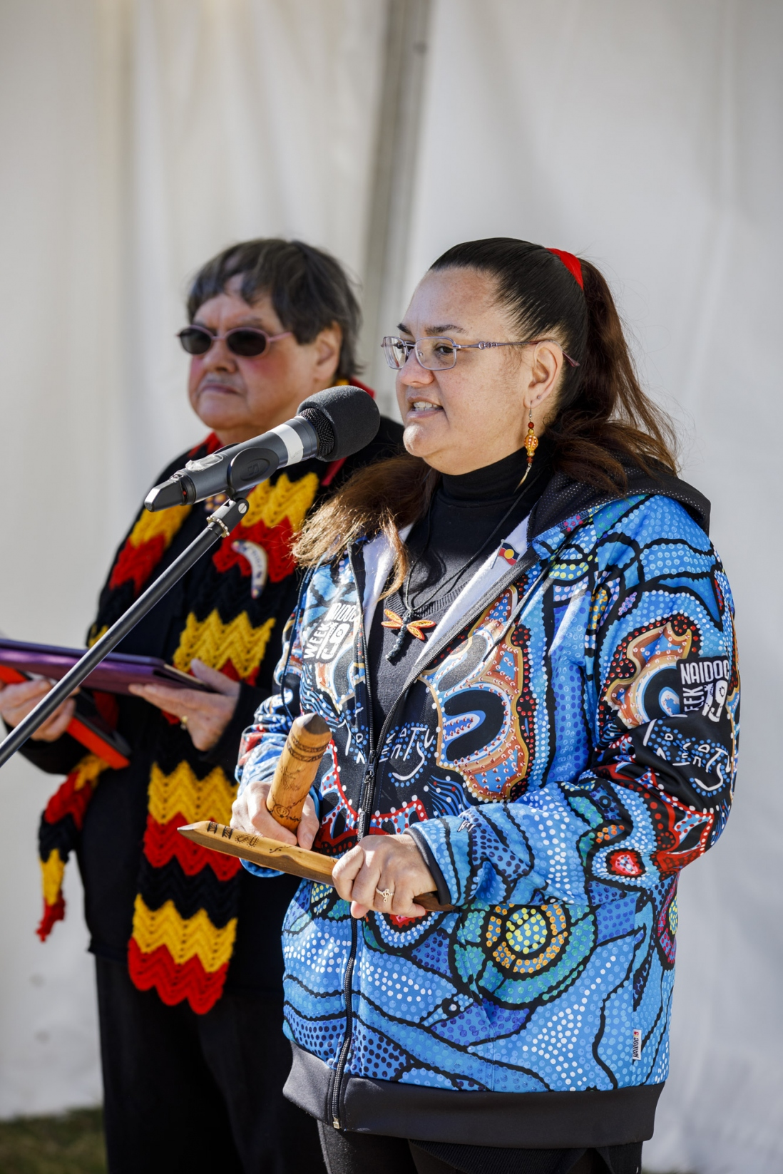 Woman holding clapsticks speaking at microphone with another woman in background; both are wearing colourful clothing.