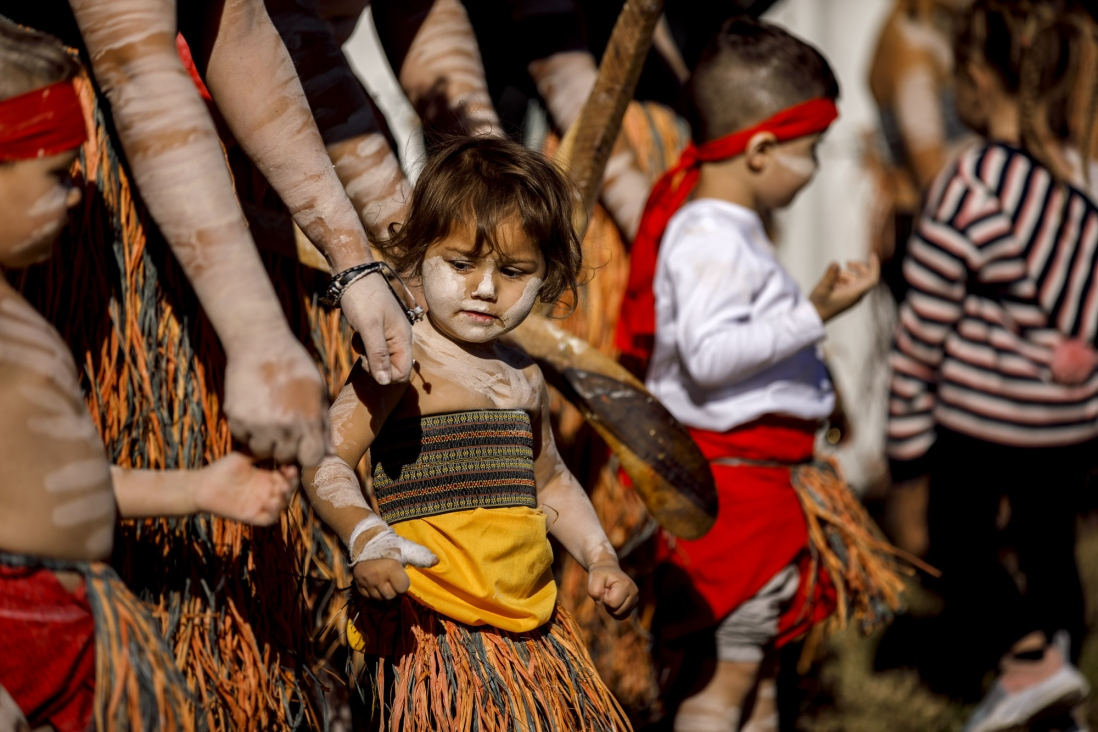 Children dancing with adults in traditional paint and dress.