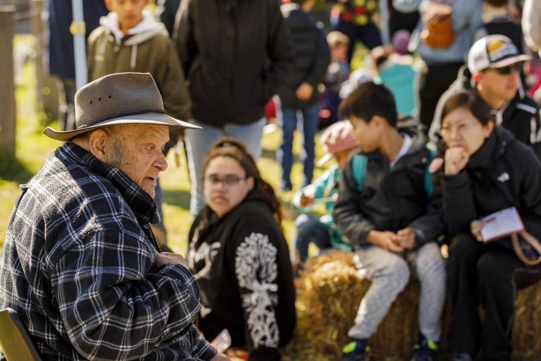 Man with hat and checked shirt talking to group.