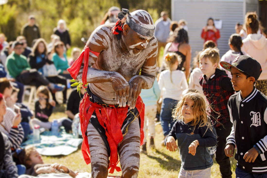 Man painted up, performing traditional dance in front of audience with child copying moves.