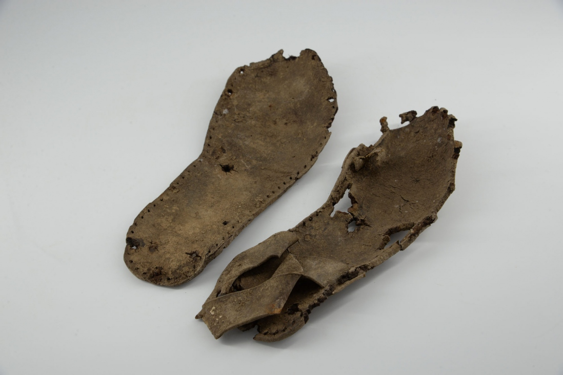 Two pieces of leather shaped for footwear.