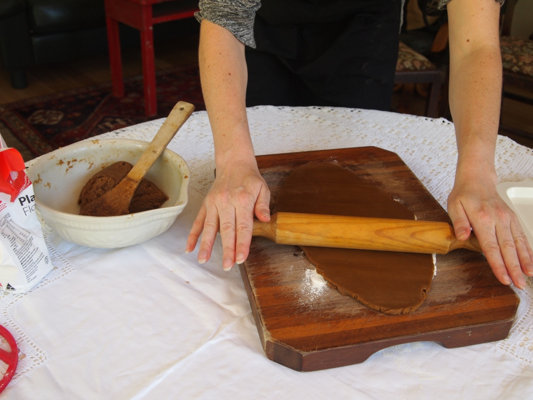 Hands rolling out gingerbread on board.