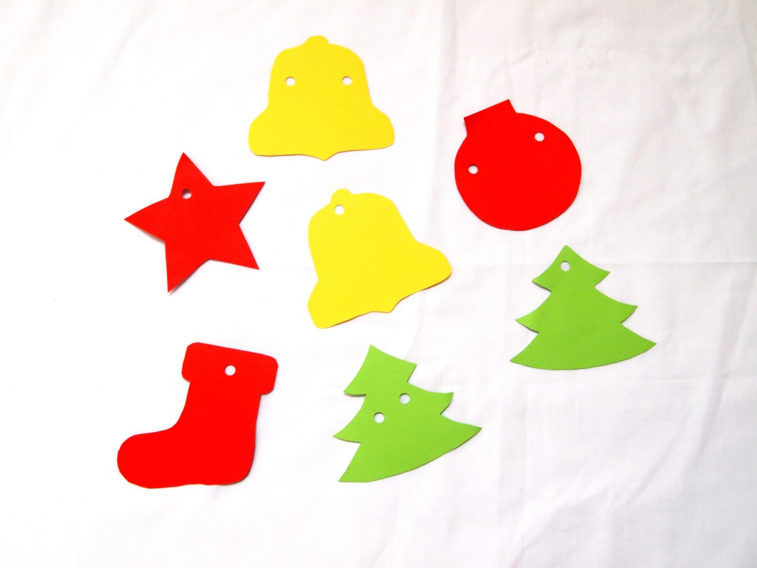Christmas themed shapes cut out from red, yellow and green coloured paper with holes punched for hanging up as decorations.