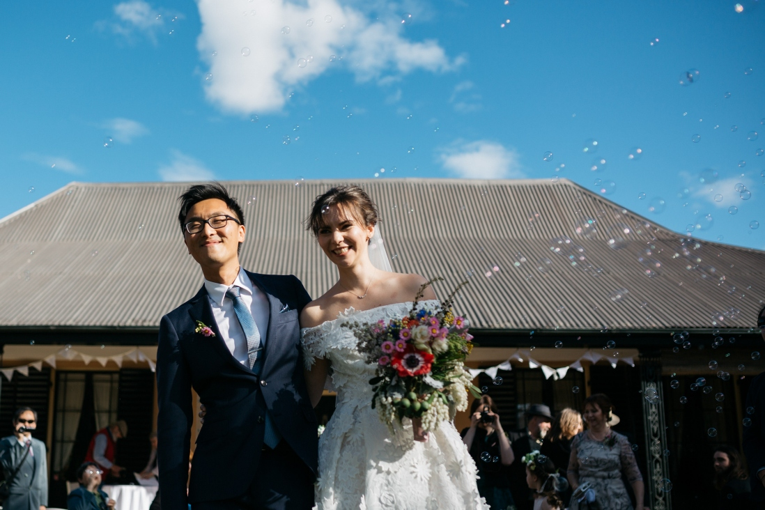 Couple in wedding clothes outside farm house.