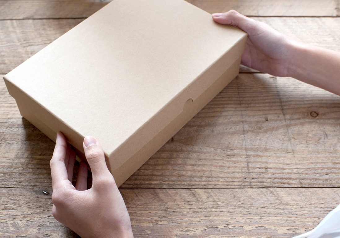Hands holding a cardboard box and lid on wooden boards