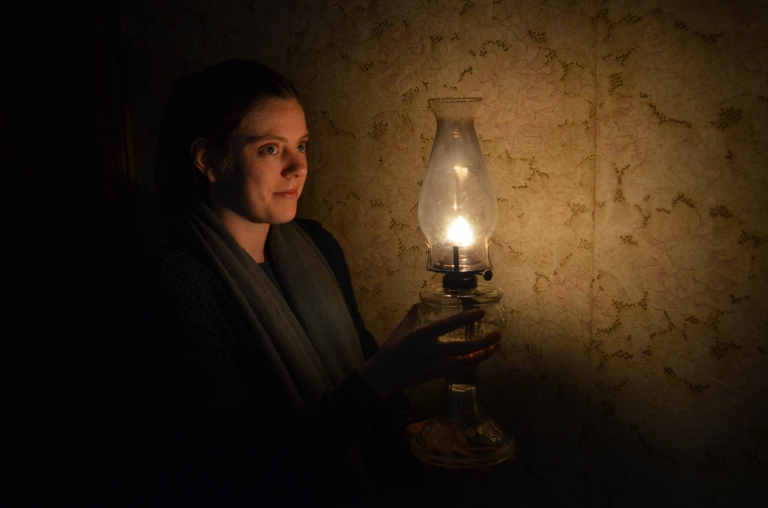 Woman holding kerosene lamp, with wallpaper in background.