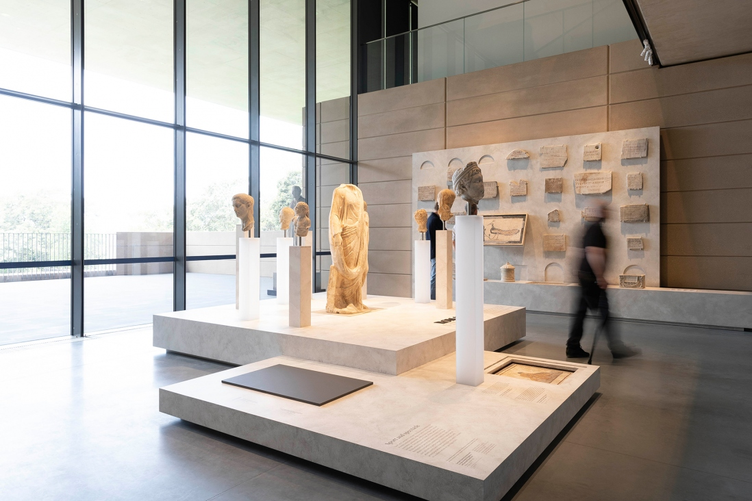 Glass cases displaying objects in backlit exhibition space with large windows.