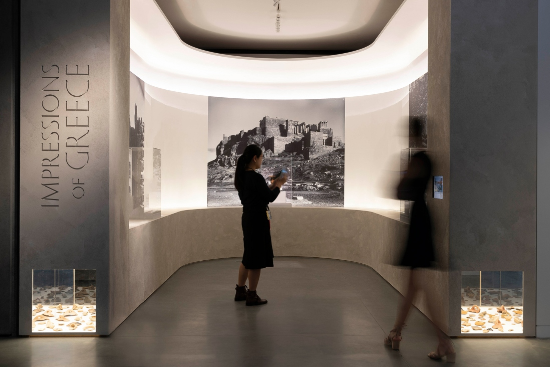 Two figures in semicircular exhibition display space backlit.
