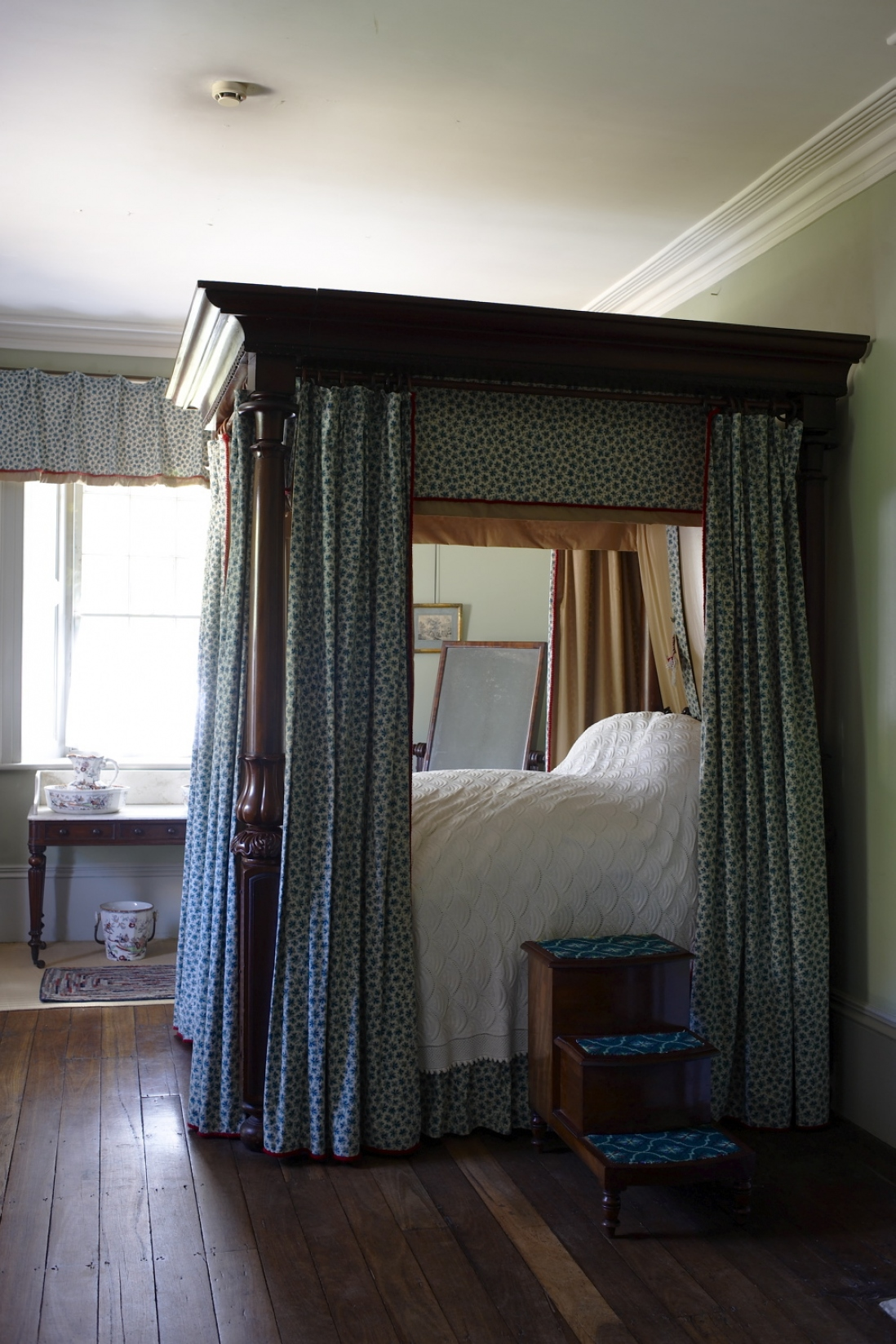 Four-poster bed with blue curtains hanging from wooden frame and wooden bedsteps at side of white covered bed, backlit by window.