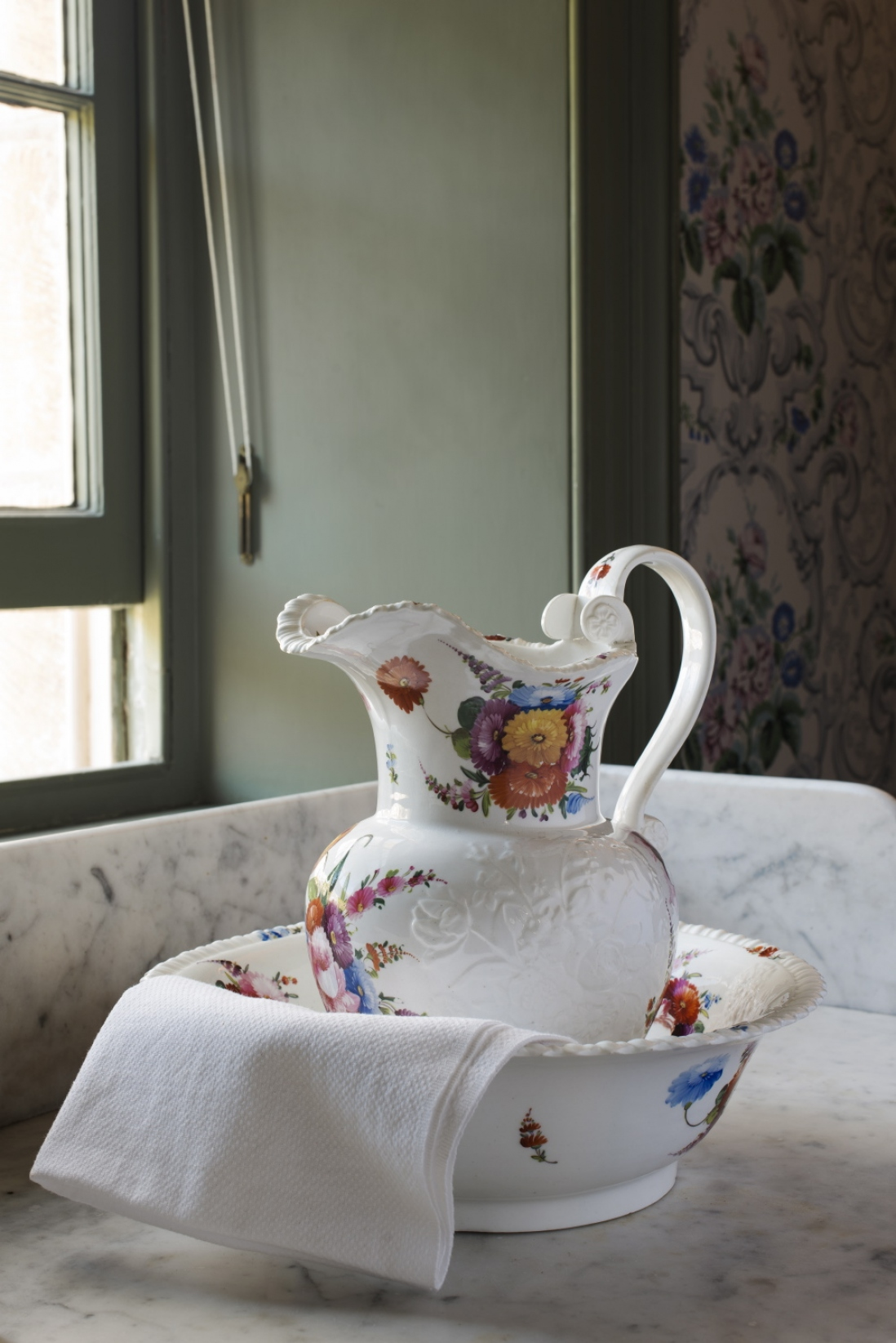 Floral-patterned white wash basin with jug and cloth inside, in front of sash window.