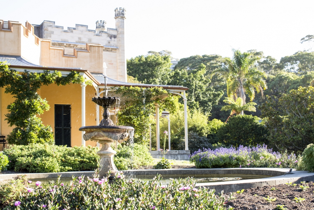 Photograph of a house and fountain in a garden