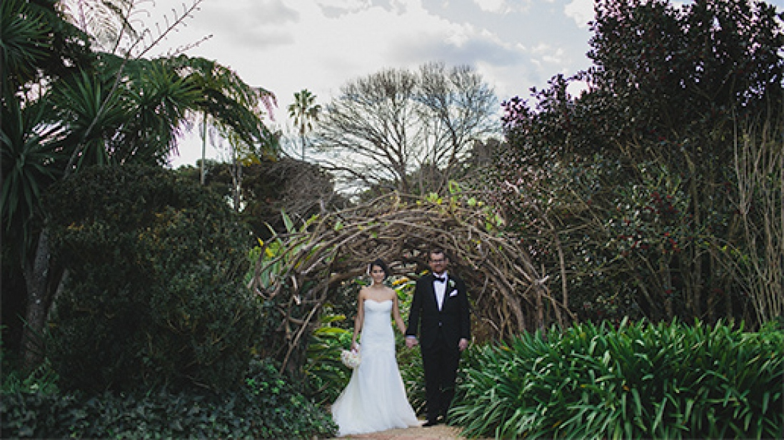 Couple in wedding clothes in garden setting.