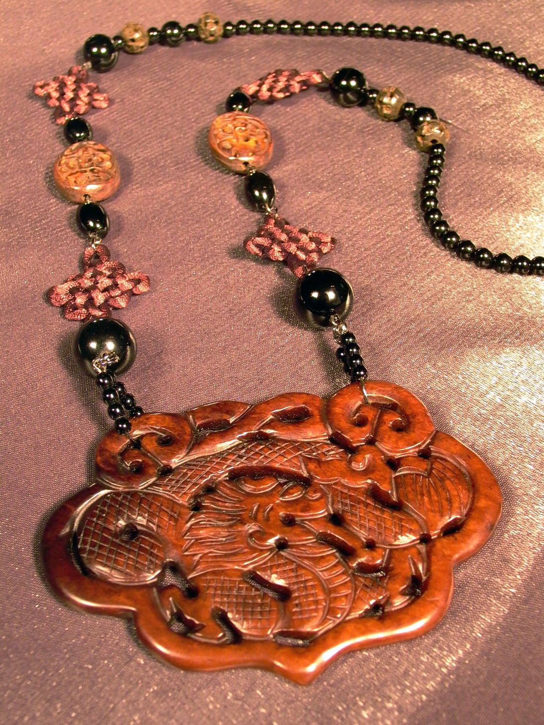This is a colour photograph of a necklace with an asian-style carved dragon pendant and gemstone beads
