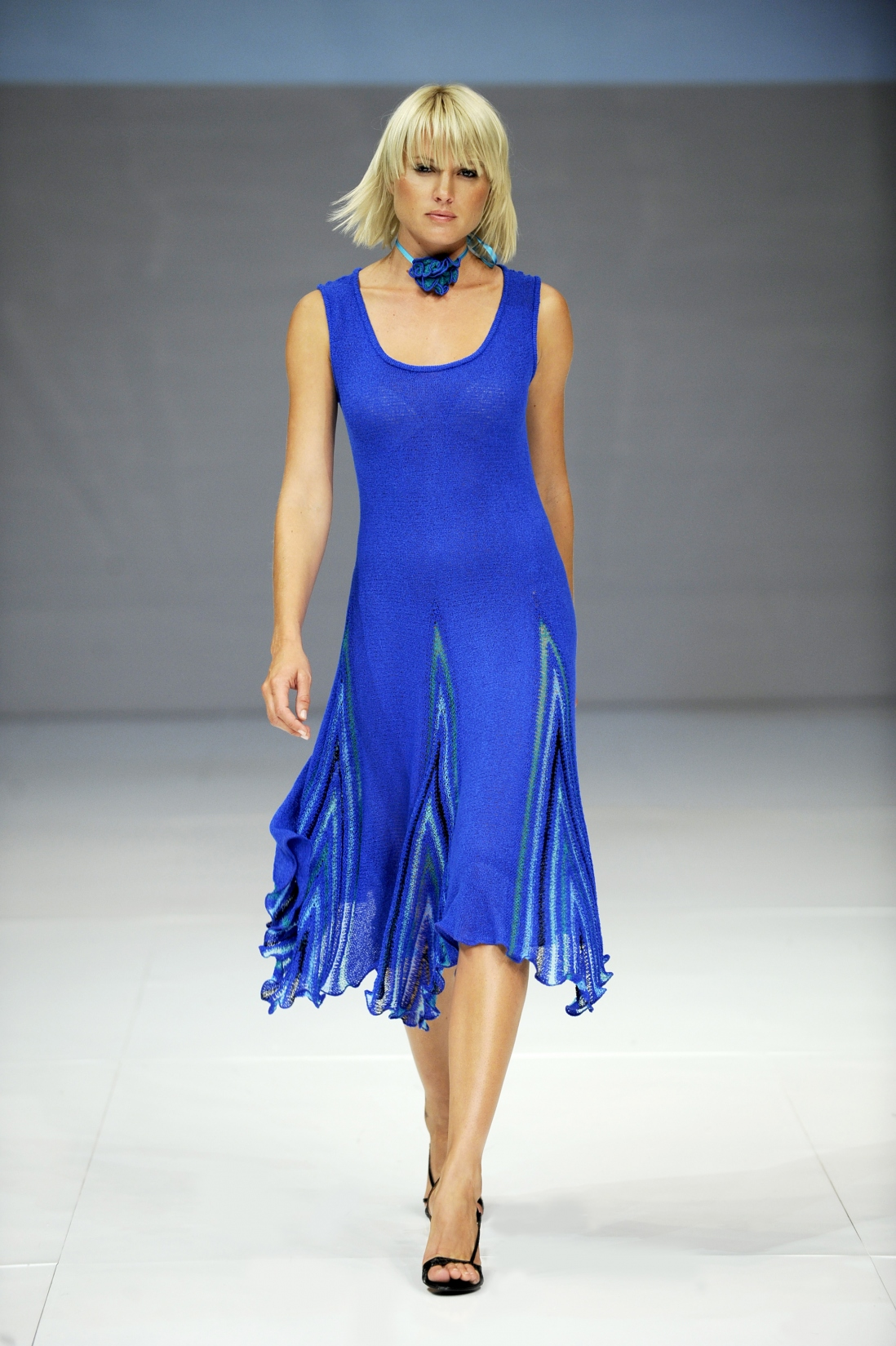 This is a photograph of a model walking down a catwalk in a bright blue soft woven dress