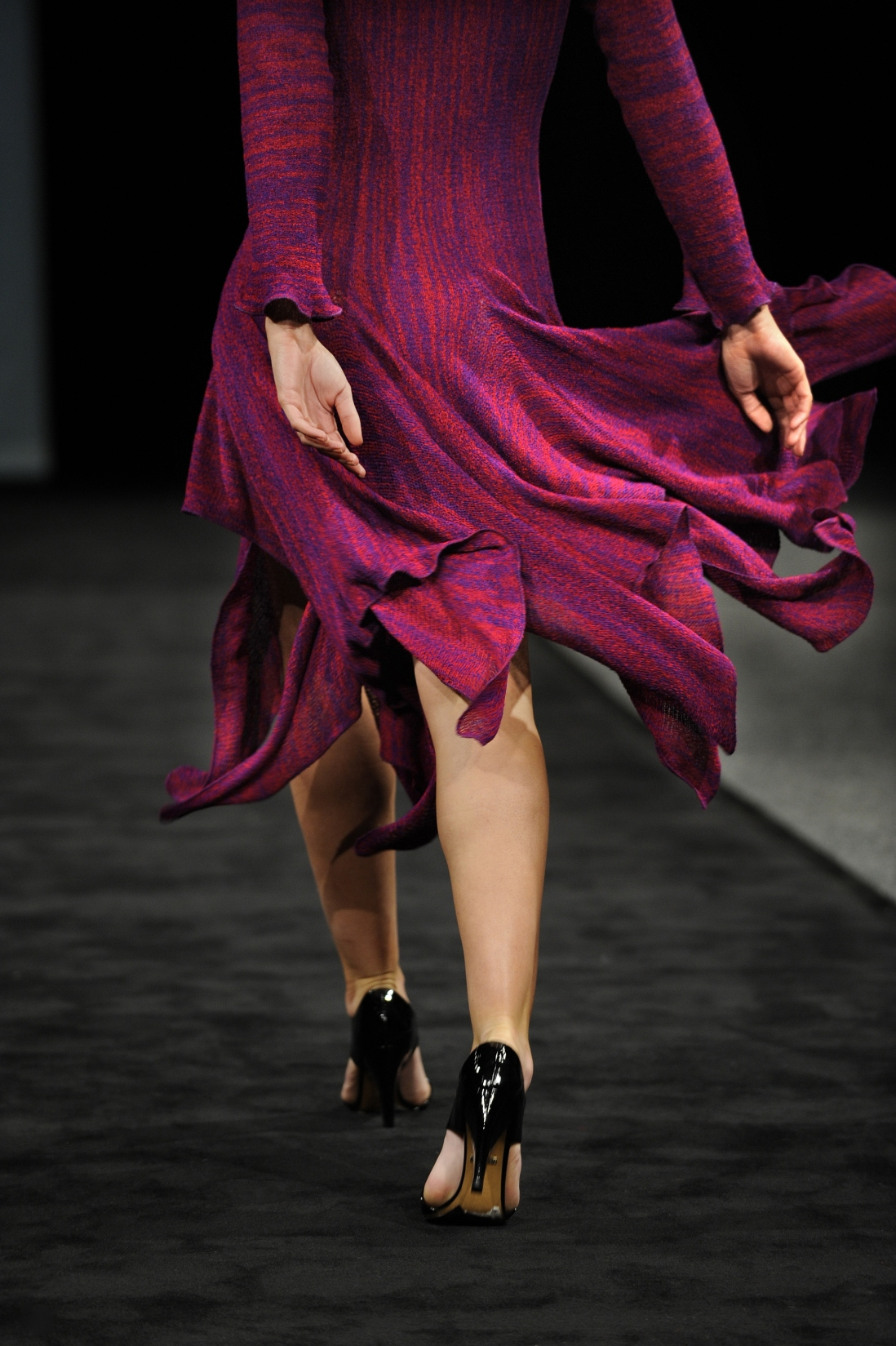 This is a colour photograph shows a woman's legs walking down a catwalk and modelling a colourful knitted dress