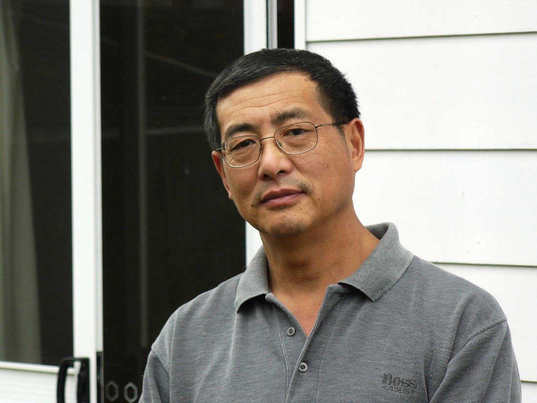 Photo of Wang Xu wearing grey shirt.
