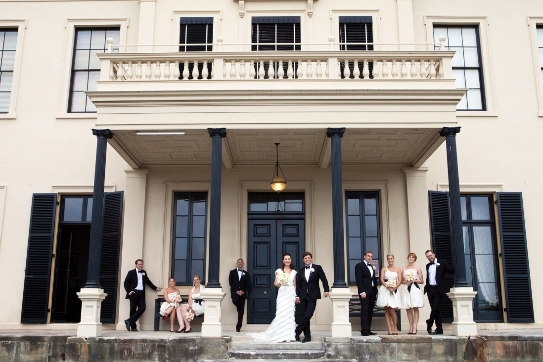 Wedding party on steps at front of house.
