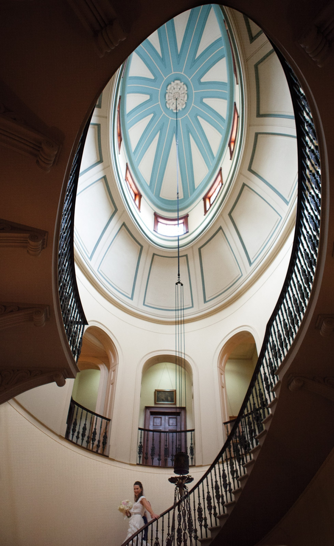 Looking up into ornate ceiling dome with spiral staircase railings.