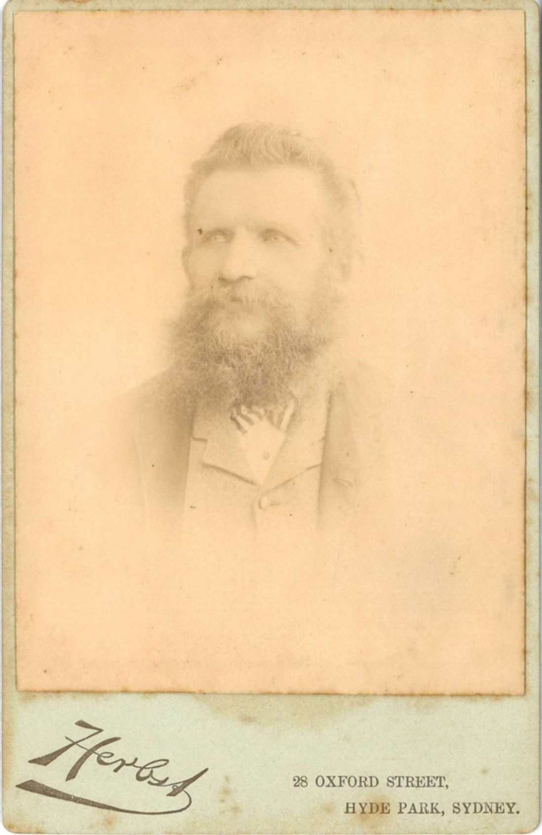 Faint photograph of bearded man.