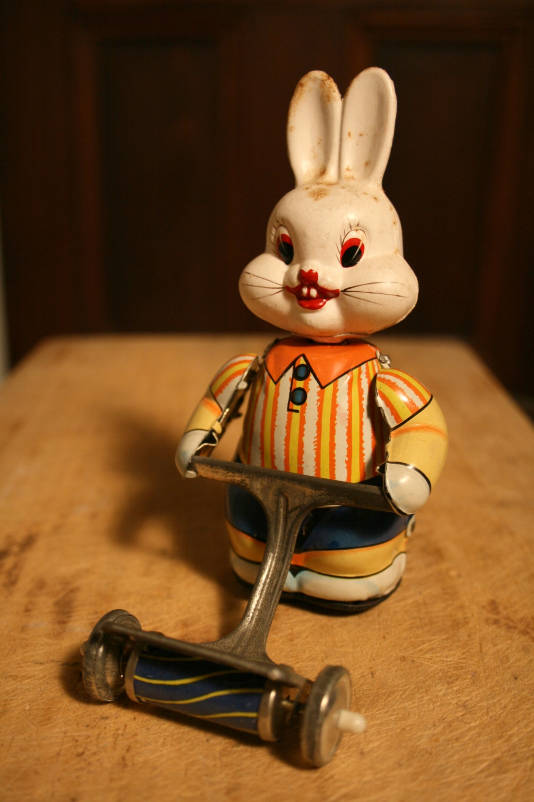 A tin white rabbit with stripped shirt pushing a lawn mower