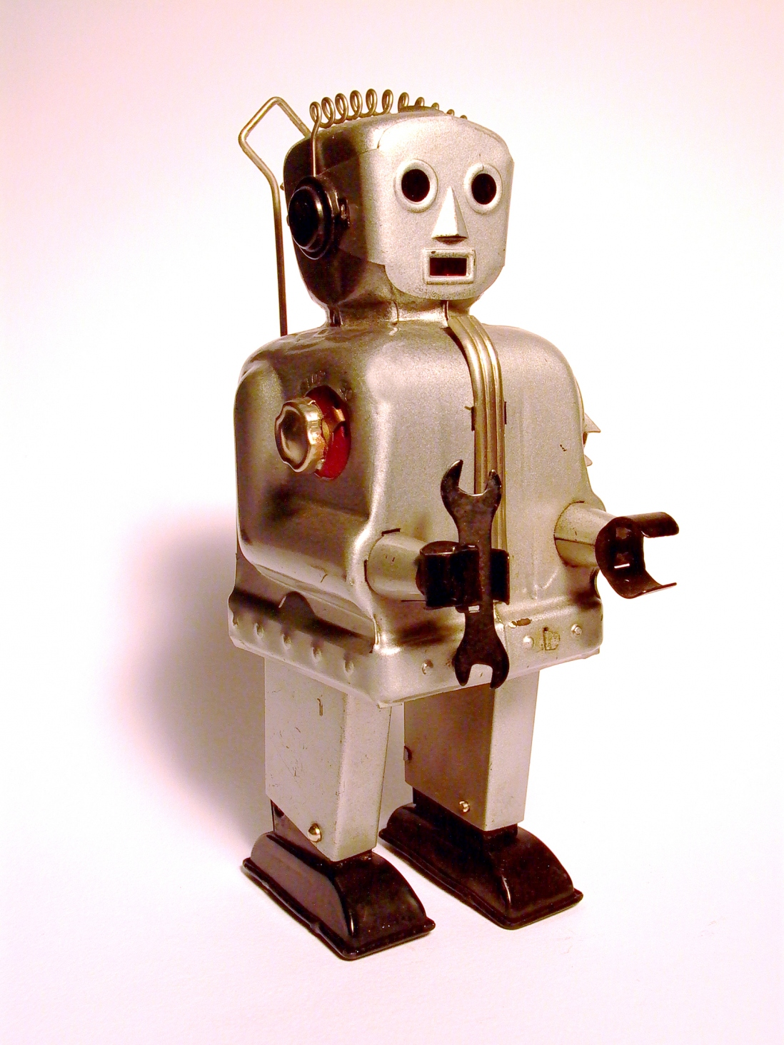 A silver tin robot armed with spanner