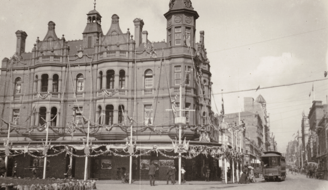 Black and white image of elaborate Victorian building with encircling veranda.
