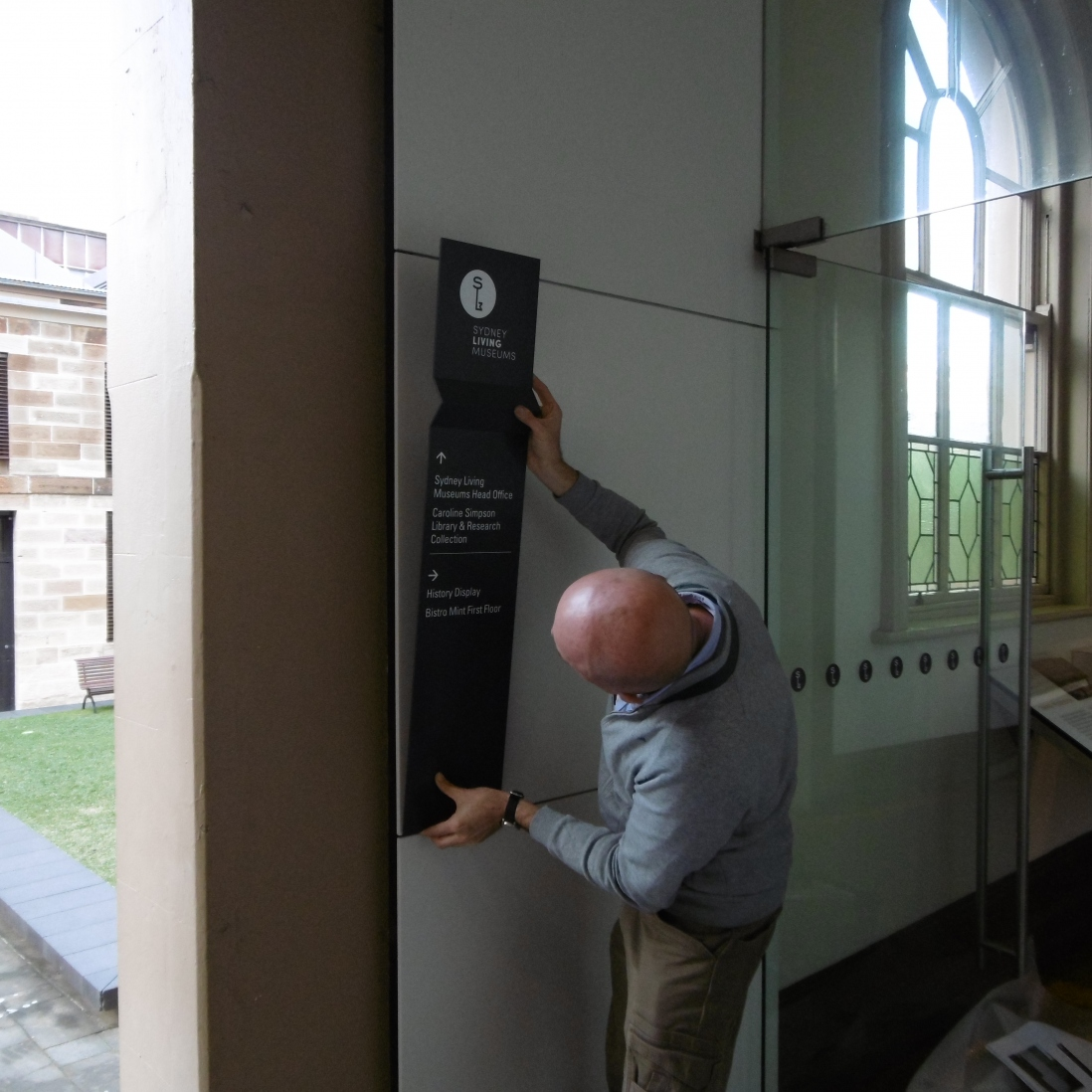 Man affixing sign to wall near door with window in background.