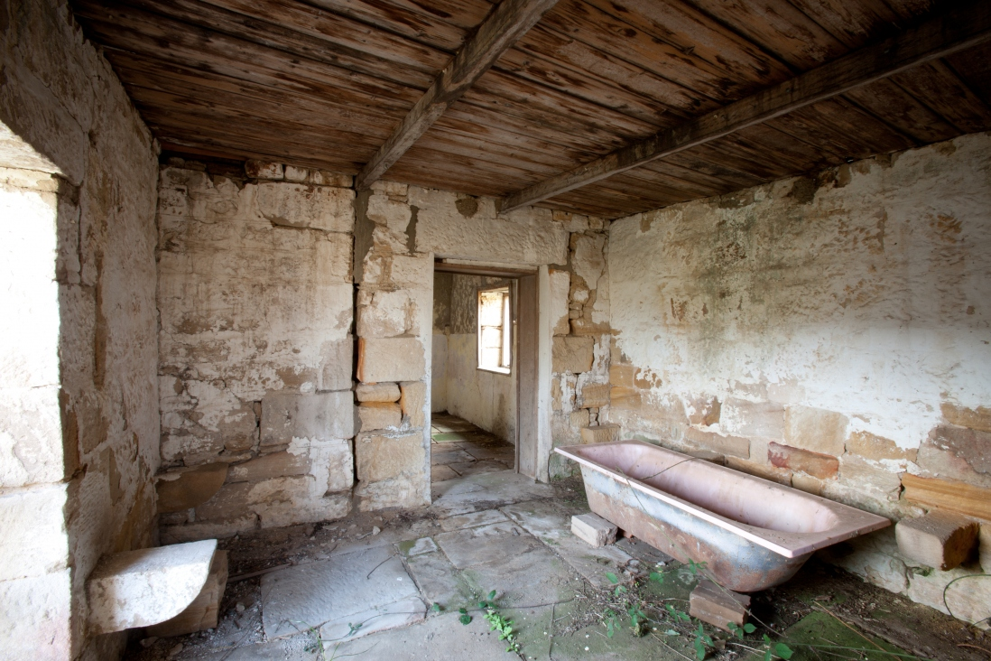 Interior of dilapidated wooden-ceiling-room with brick walls, a white trough and dirt floor with open doorway.