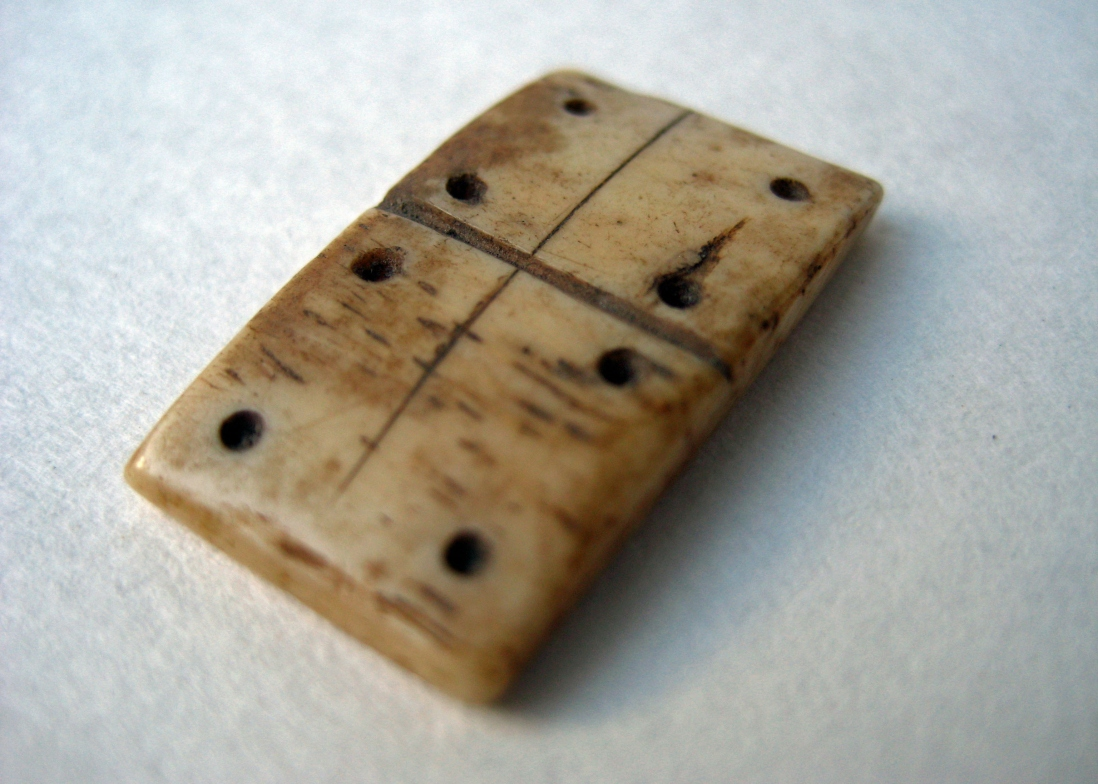 Domino game piece carved from bone showing double 4 dots on white background