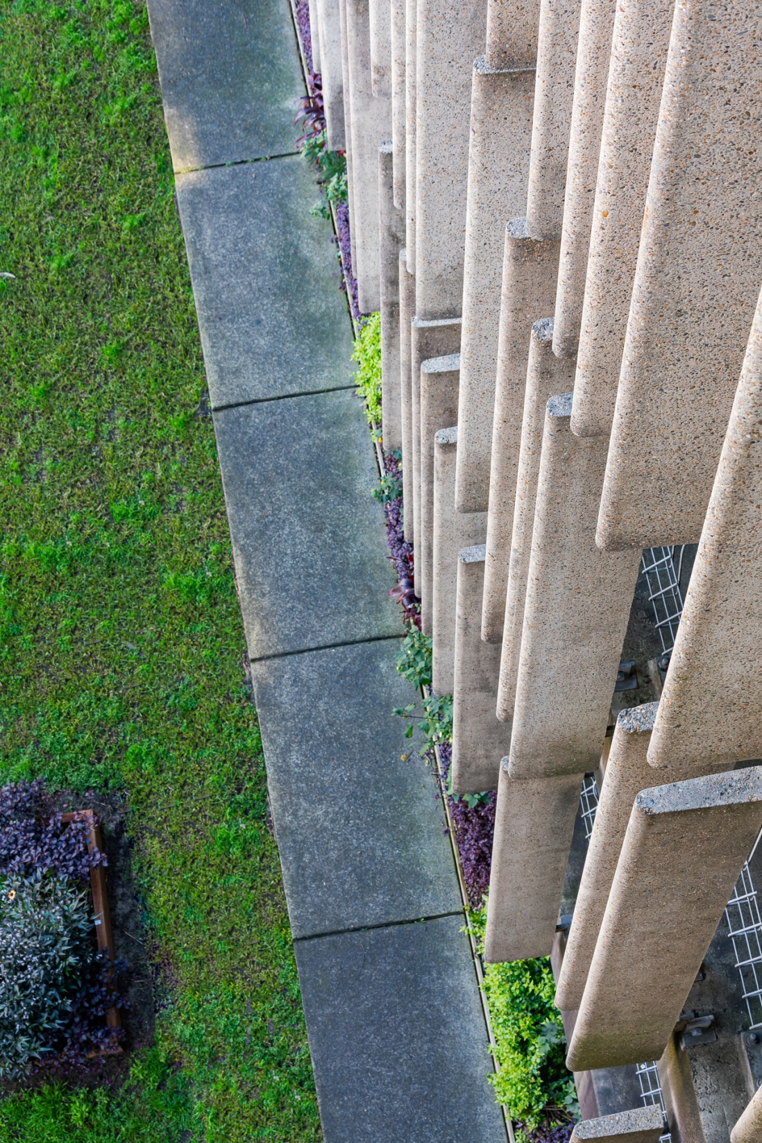 View looking down on an angle over the front of a building with some grass at the bottom.