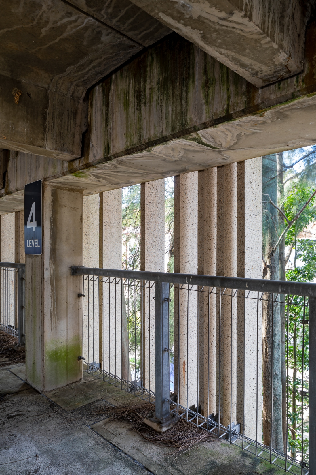 View looking out through the facade of the Cross Street Parking Building with water markings visible in the concrete