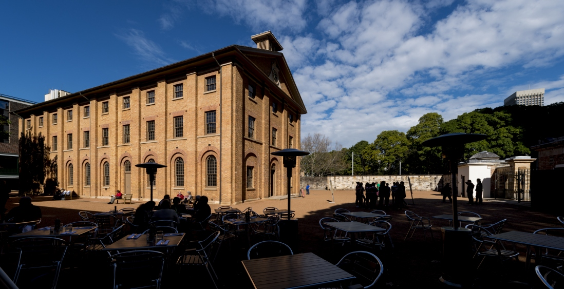 Large brick building looms over a gravel courtyard with people gathered in groups in various locations.