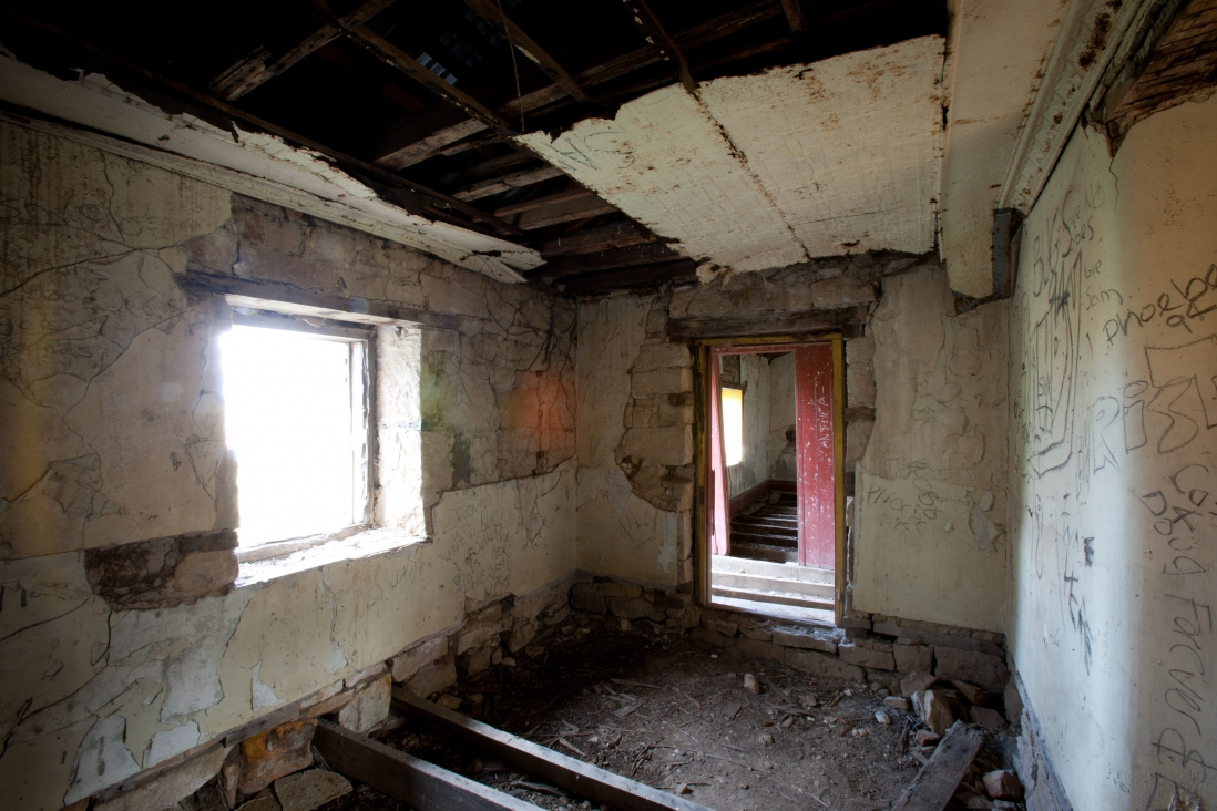 Run down room with exposed roof beams, window to left and steps down, with door in back wall with light from another window.