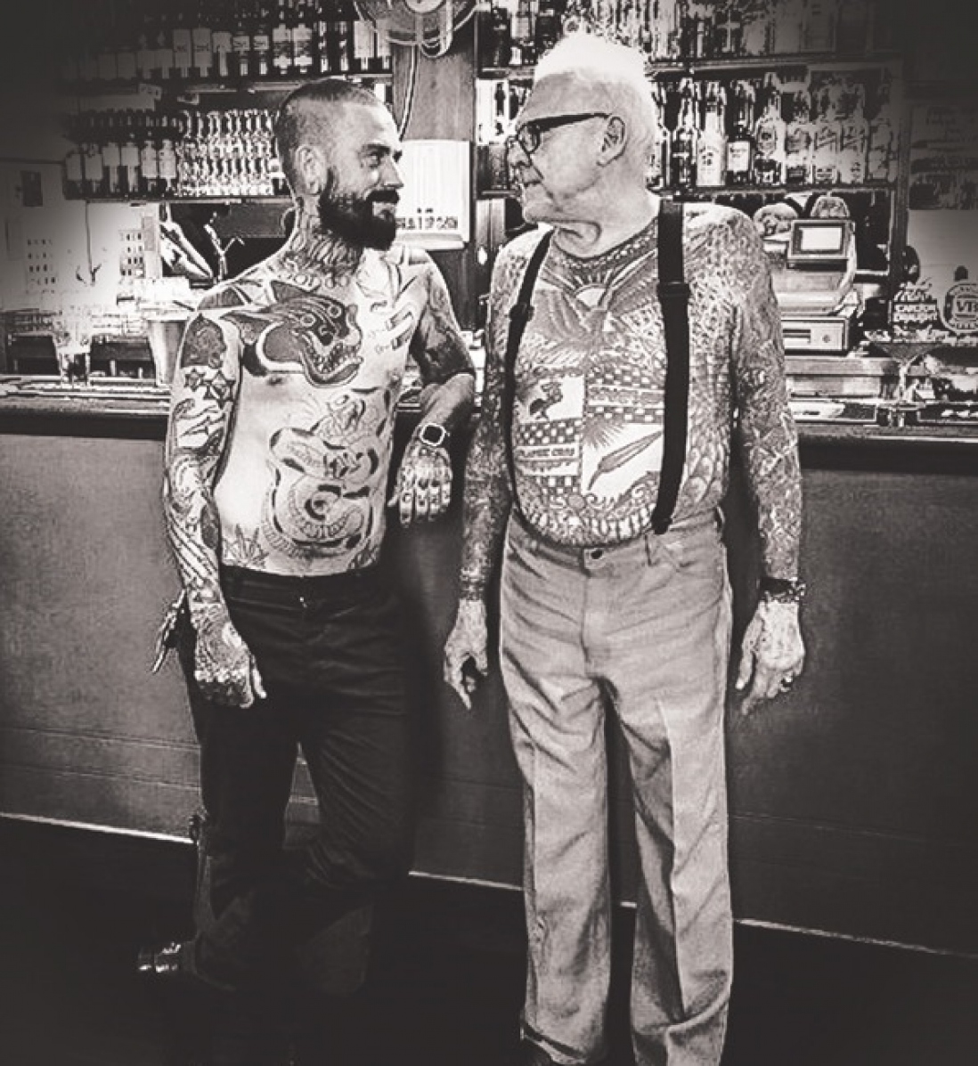 Two men at a bar, shirtless, showing their tattoos.