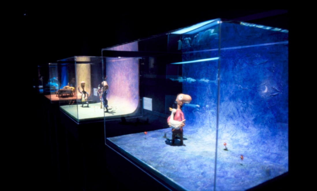 A shot showing several dioramas used to make the animations. A character stands in the first case holding a duck.