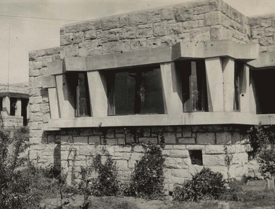 Black and white photo of sandstone house facade.