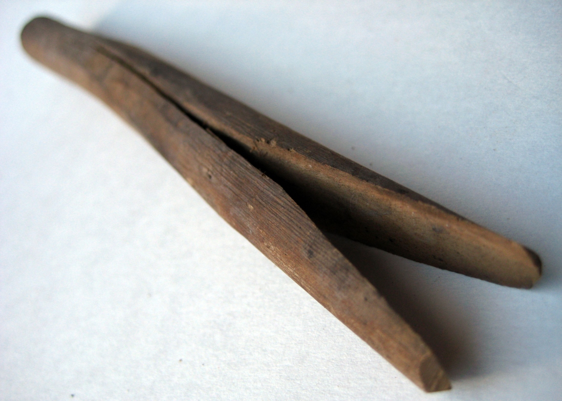 Wooden peg, improvided from tree branch against white background