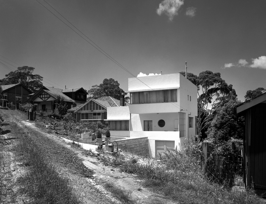 Black and white photograph of a white box modernist house.