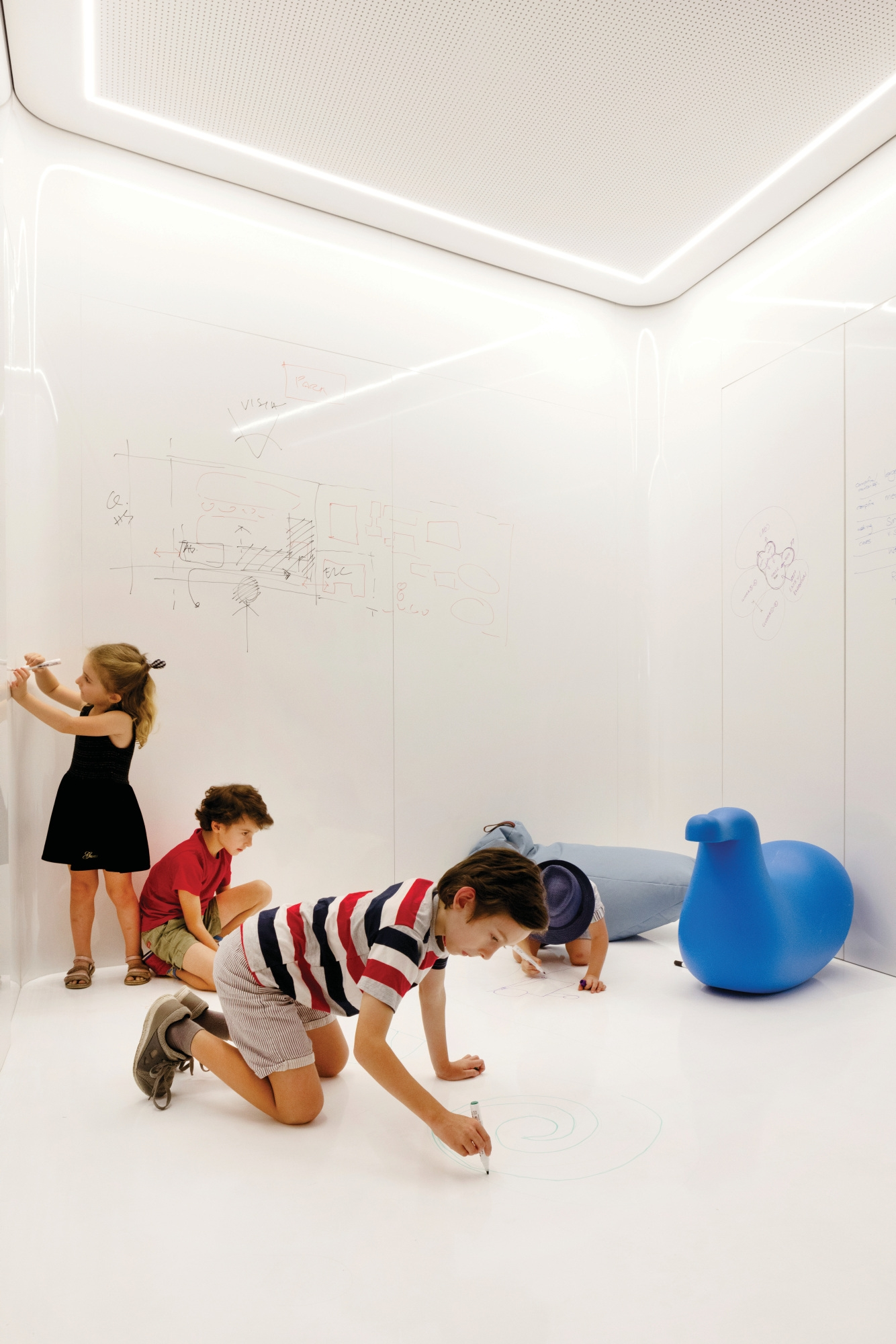 White room with children drawing on walls and floor.