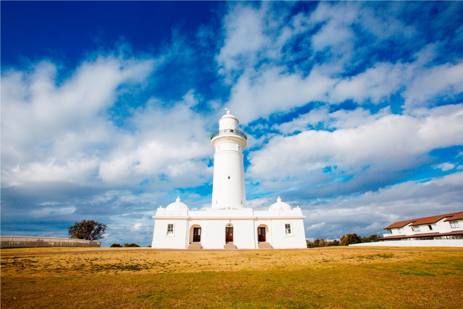 White lighthouse and outbuildings against blue sky.