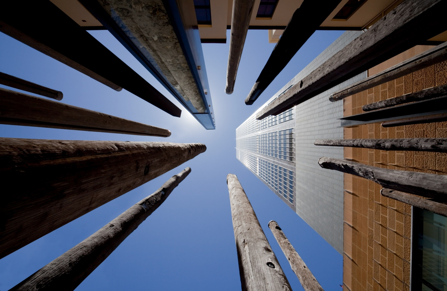 Looking up at sky from below sculptural elements, with tall building and sunlight reflecting.