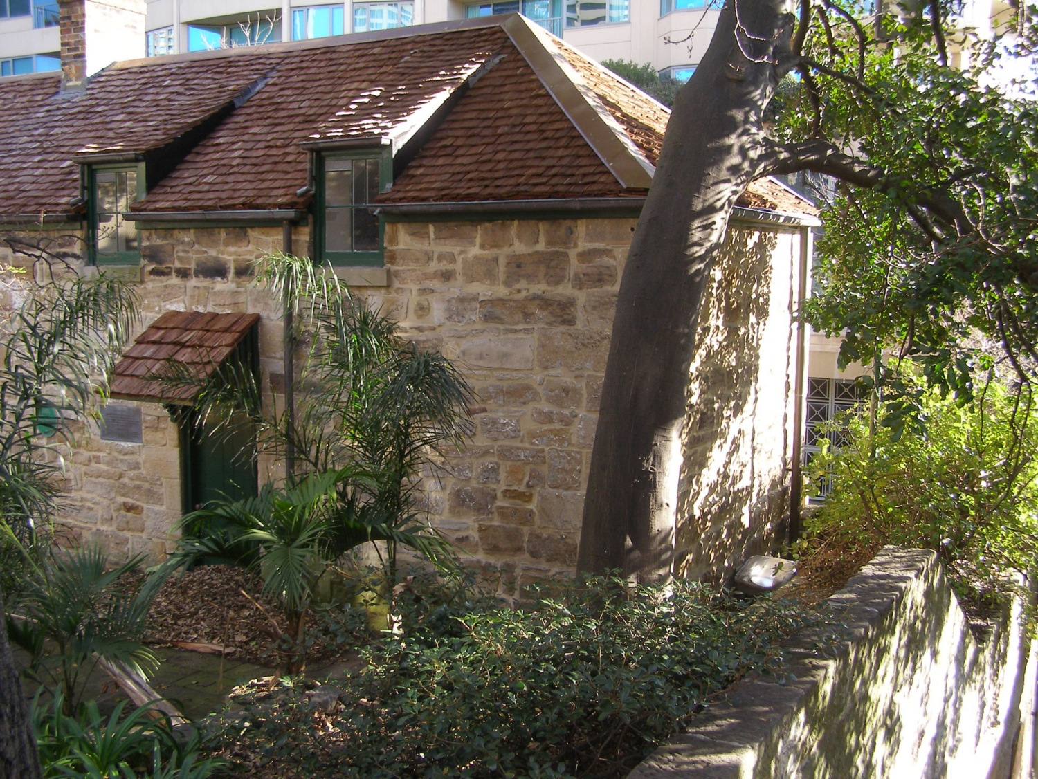 View of sandstone walled cottage with trees.