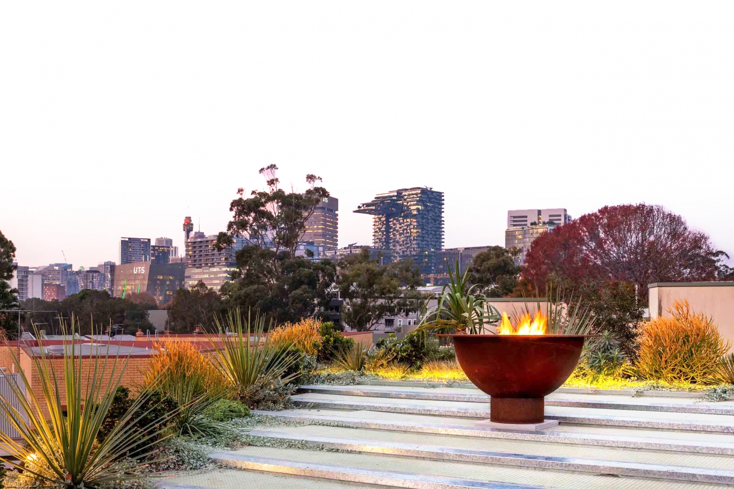 Courtyard amongst trees with a brazier, looking out over a cityscape.