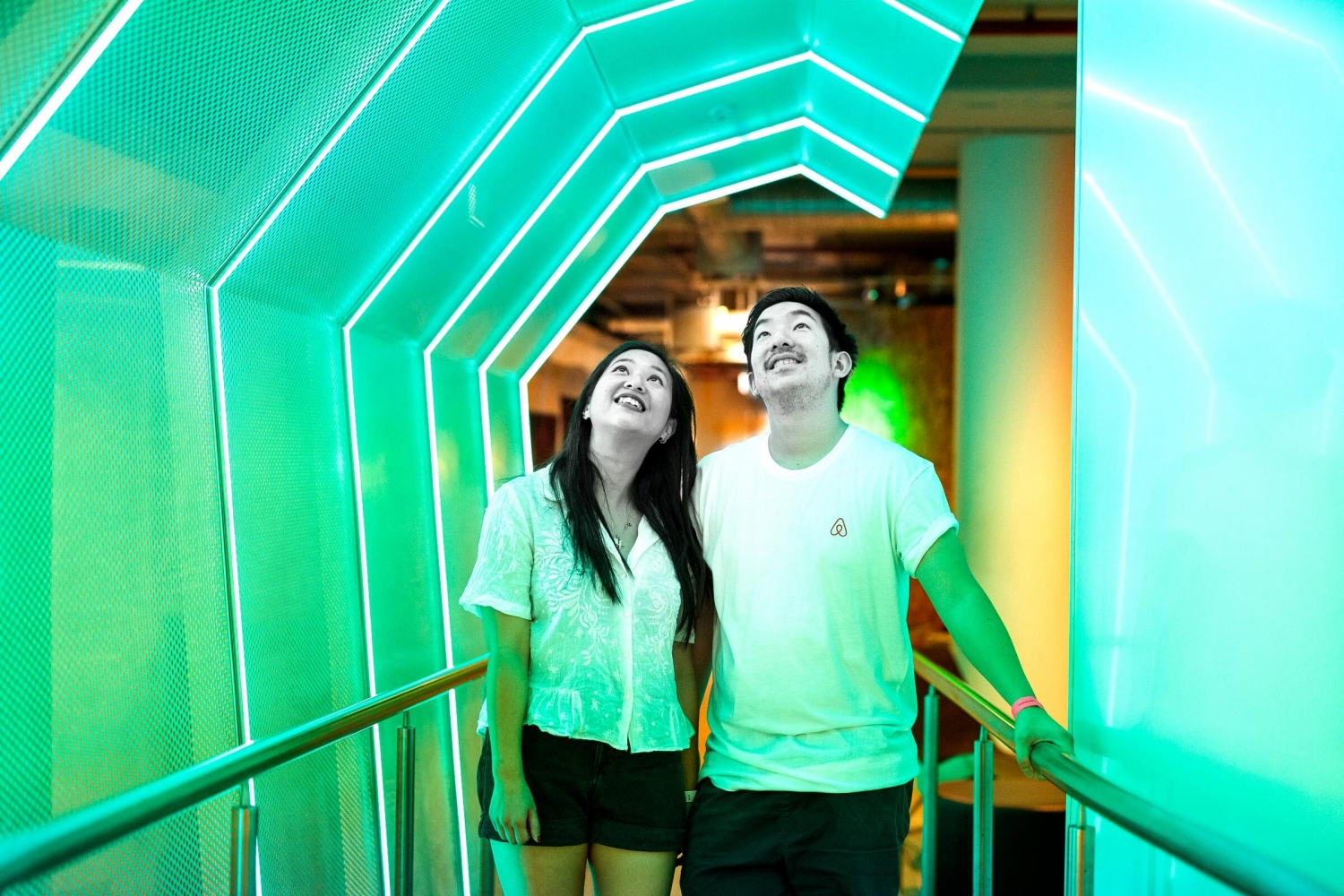 A man and woman in a tunnel lit by green light