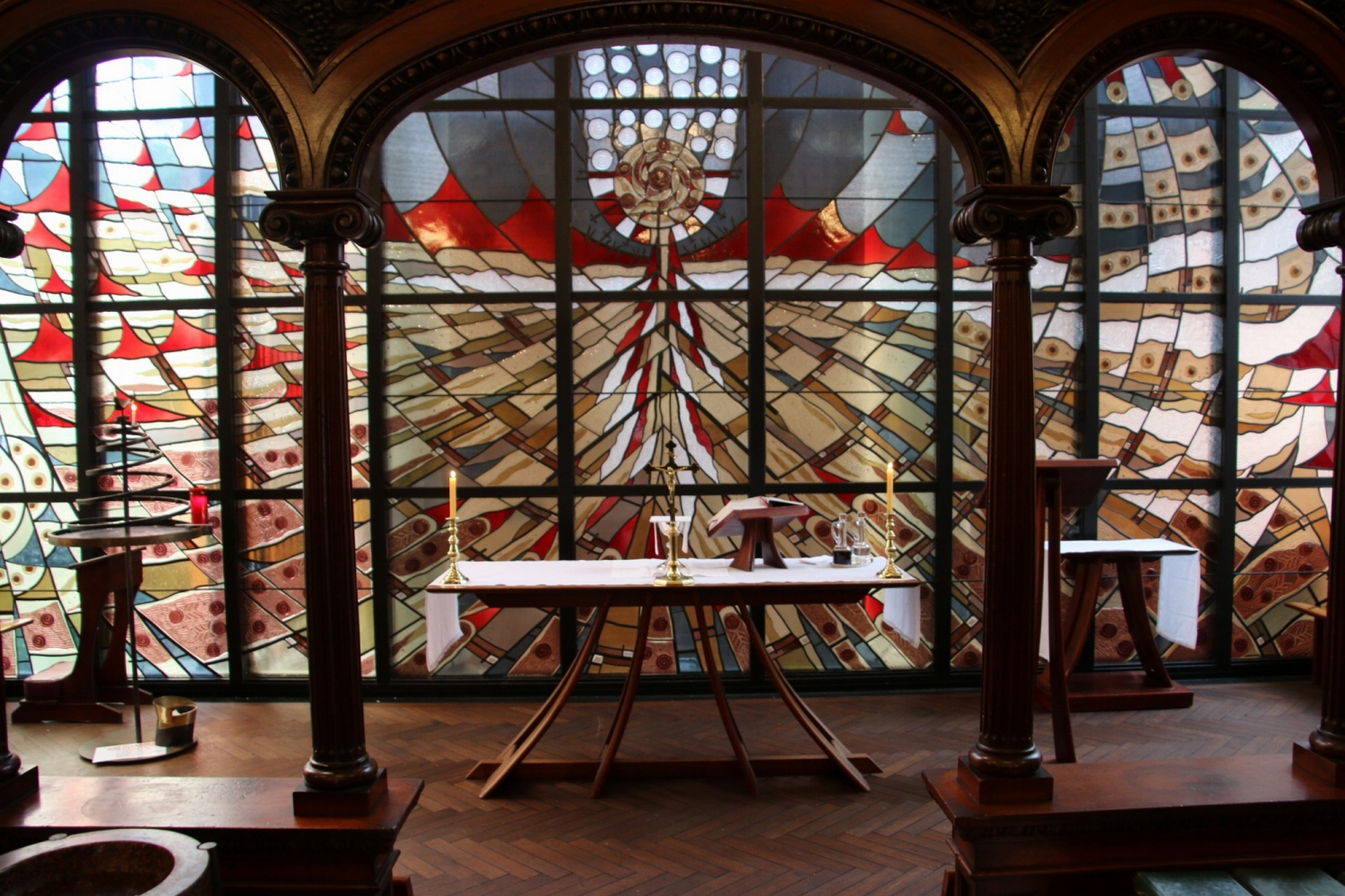 Backlit stained glass windows framed by arches.